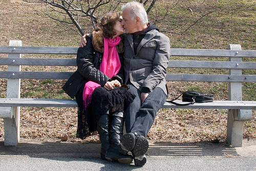 Adorable Older Couple Kissing On A Park Bench In Scarves